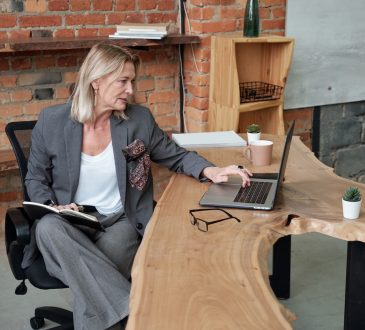 Serious mature business woman in gray suit sitting at wooden desk and checking data on laptop in office