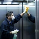 Male cleaner disinfecting elevator