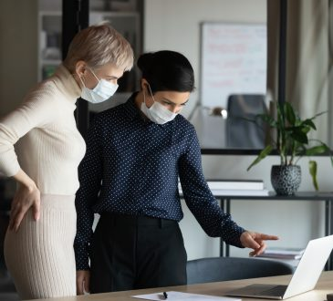 two businesswomen in face masks in office looking at laptop screen