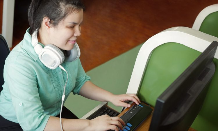 Woman with visual impairment wearing headphones using computer with refreshable braille display