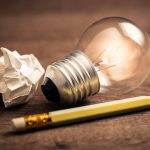 Pencil with glowing light bulb and crumpled paper on wood table