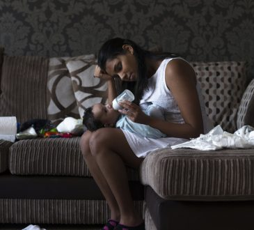 Stressed young mother sitting on her sofa whilst feeding her baby son.