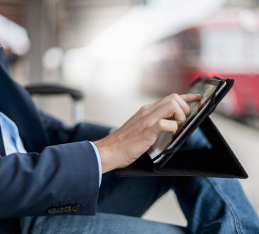 man sitting and using tablet