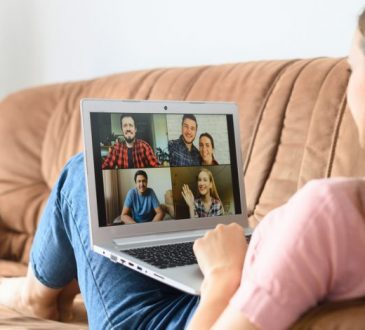 woman sitting on couch during video call on laptop