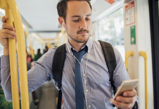 man looking at phone on bus