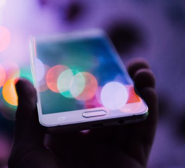 person holding up cellphone with coloured lights shining on screen