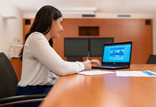 woman using laptop on board room table