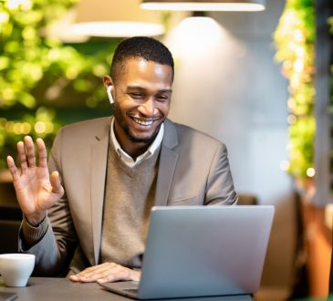 businessman watching video on screen and waving