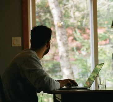 man working at kitchen table and looking out window