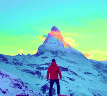 man approaching mountain summit with colourful sky surrounding