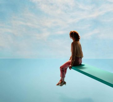 woman sitting on end of diving board over ocean