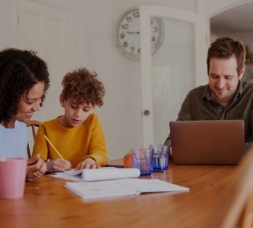 father works on laptop as mother helps son with homework at kitchen table
