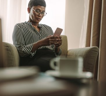 woman reading on cellphone on couch