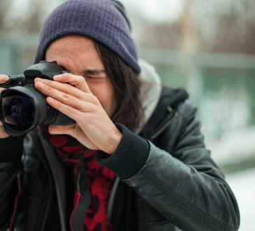 young person taking photo with dslr camera outside