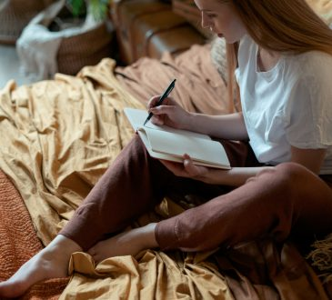 woman writing in journal on bed