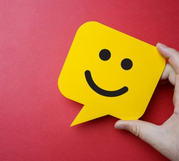 hand holding yellow sticky note with smiley face on red background