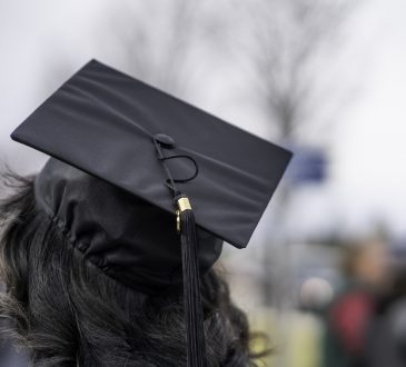 university student with long dark hair wearing mortarboard, from behind