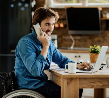 man in wheelchair working on laptop at kitchen table