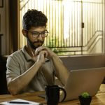 man watching video conference on laptop