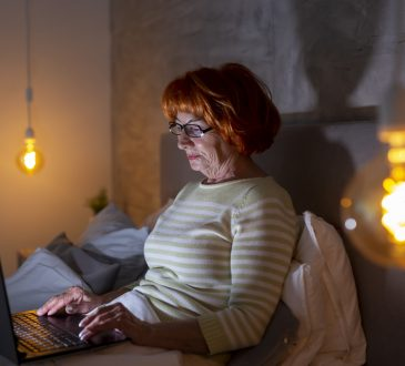 woman sitting in bed watching video on laptop