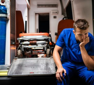 A pensive paramedic sitting on the edge of an ambulance car.