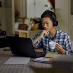 male student watching laptop drinking tea