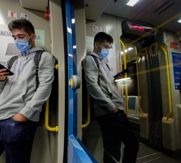 Young man wearing a face mask traveling on the Porto subway