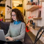 young woman sitting on bench in office working on laptop