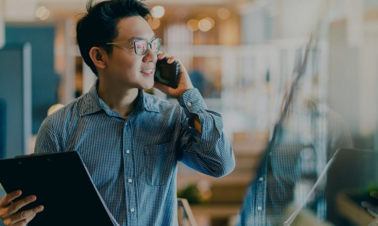 man holding clipboard and talking on cellphone in office