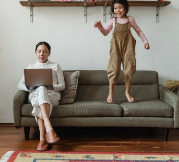 mom working on laptop while child jumps on couch