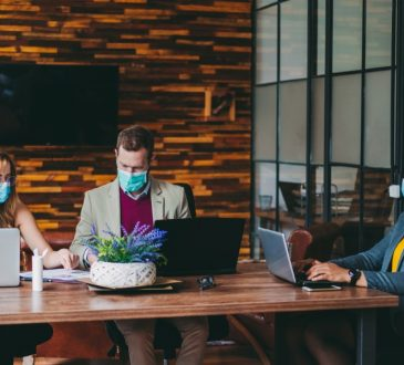 three people working on laptops at table wearing mask