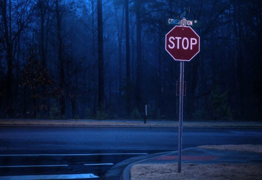 stop sign on dark road