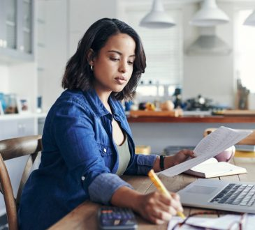 woman doing work at kitchen table