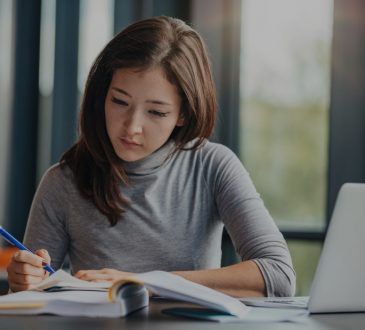 woman writing in notebook in front of laptop