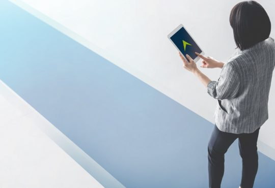 photo illustration of woman walking on blue pathway carrying tablet with arrow on screen