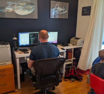 man sitting at home computer with son beside him on laptop
