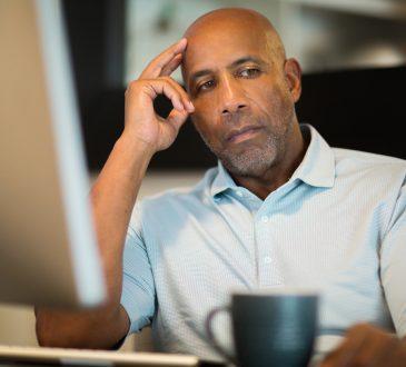 man sitting at desk looking depressed