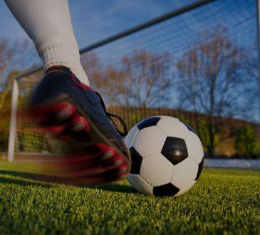 close up of foot kicking soccer ball toward empty net