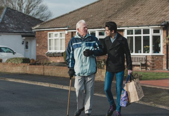 young man helping old man carry groceries