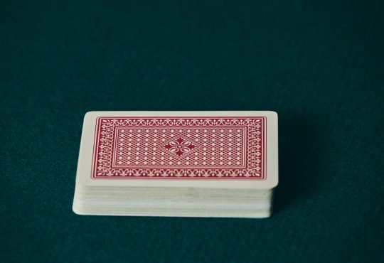 a deck of red cards on the green game mat