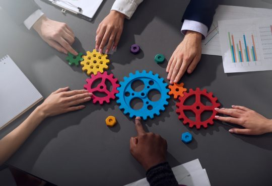 Teamwork of businesspeople work together and combine pieces of gears