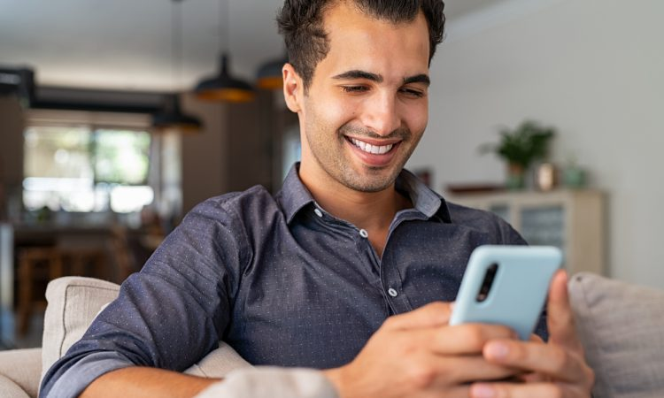 Cheerful businessman using smartphone while sitting on sofa at home.