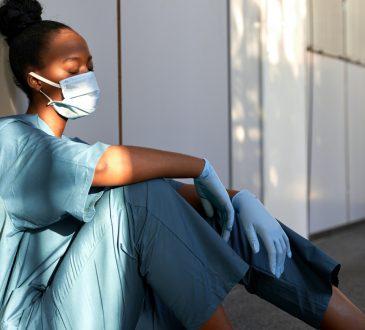 exhausted nurse sitting on floor of hospital hallway