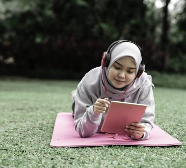 student lying on grass looking at tablet
