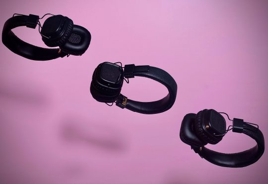 three pairs of headphones floating on diagonal line on purple backdrop