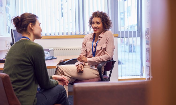 Female College Student Meeting With Campus Counselor
