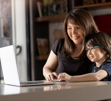 Mother and boy studying with laptop in home.