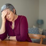 older woman looking stressed sitting at kitchen table