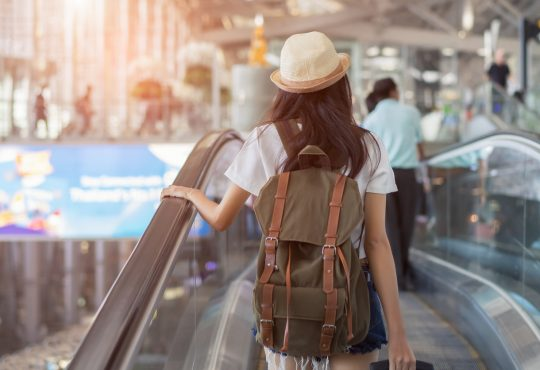 woman with backpack in airport terminal on escalator
