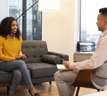 Woman Sitting On Couch Meeting With Male Counsellor In Office